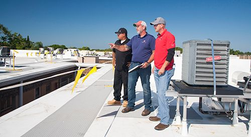Click image of roofers on Florida Commercial Roof to open Commercial Roof Replacement Services page.