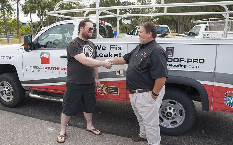 Mr. Bostic shaking hands with Brian Wallace, President of Florida Southern Roofing.