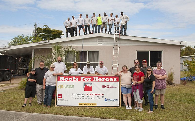 The Florida Southern Roofing team that participated in the 2019 Roofs for Heroes project and Mr Bostic and his family.